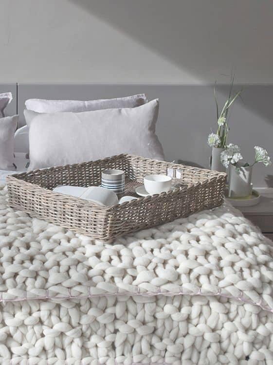un lit cocooning avec un plaid a grosses mailles