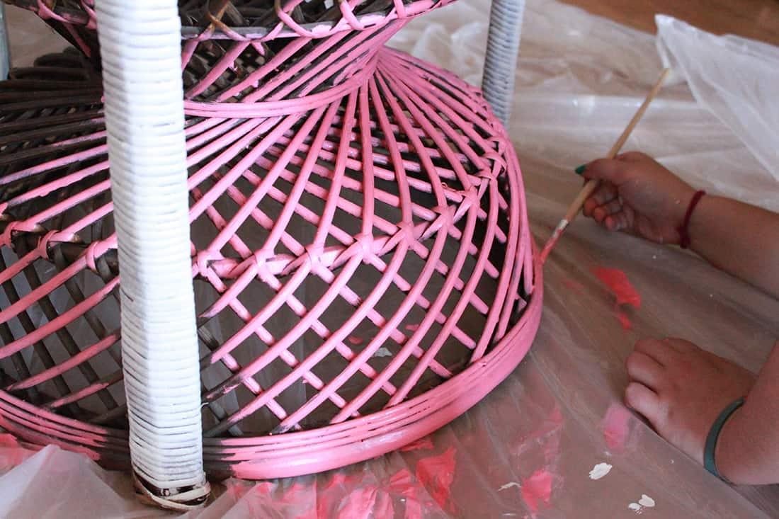 pose de la peinture rose sur le pied du fauteuil rotin - Repeindre un fauteuil rotin de style Emmanuelle