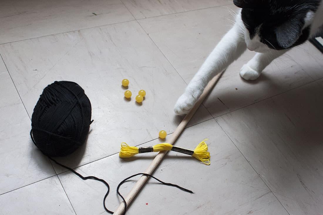 un chat qui joue avec les perles du macrame
