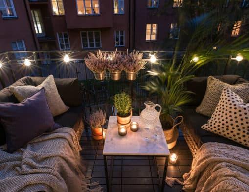 balcon avec des canapés et des guirlandes lumineuse