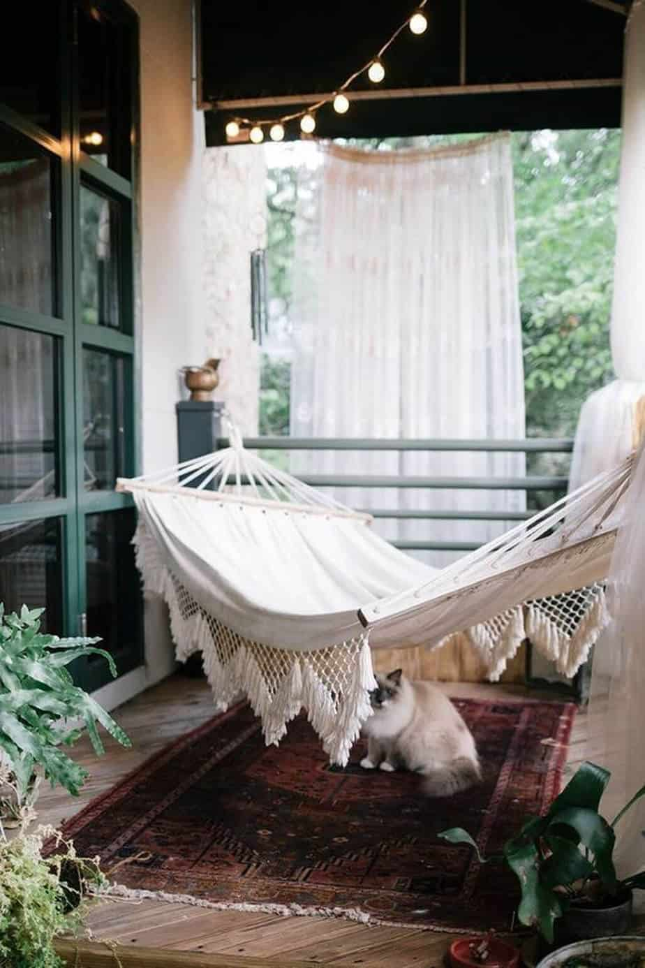 balcon avec décoration bohème contenant hamac et tapis