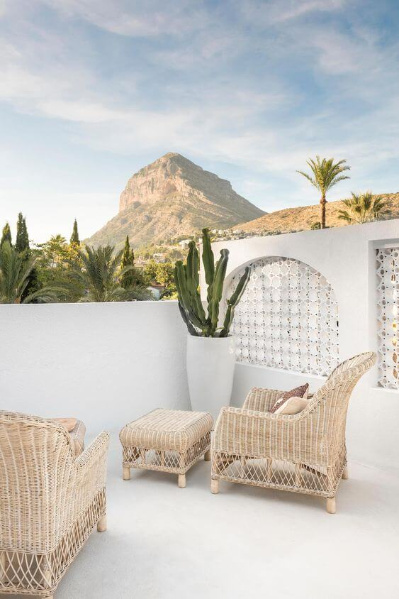 terrasse boheme avec fauteuil en rotin et sol en béton  - Quel matériau pour ma terrasse choisir ?